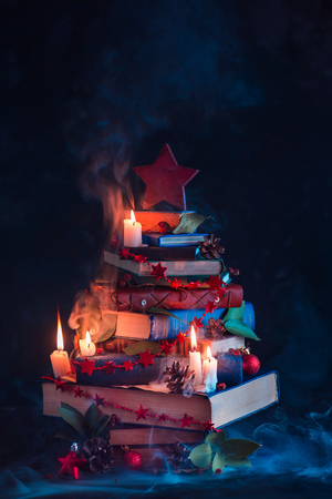 Christmas tree made out of books with candles and mysterious smoke. Winter decorations for readers and nerds concept