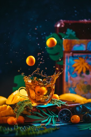 Citrus tea with a dynamic splash. Mango, oranges, kumquat, and other tropical fruits in a dark still life with copy space.
