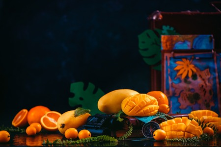 Mango, oranges, kumquat and other tropical fruits on a dark background with copy space. Traveling for the discovery of exotic fruits concept. 写真素材
