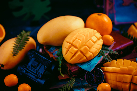 Mango close-up with oranges, kumquat, and other tropical fruits. Dark background with copy space. Traveling and discovery of exotic fruits concept. 写真素材