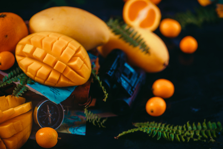 Cut mango halves close-up header with oranges, kumquat, and other tropical fruits. Dark background with copy space. Discovery of exotic fruits concept. 写真素材