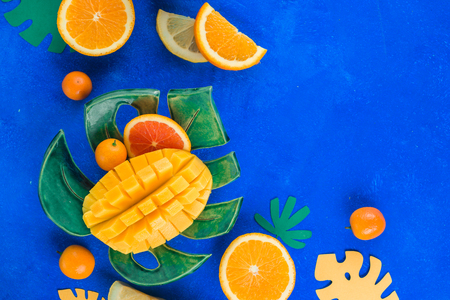 Exotic fruits flat lay. Mango, oranges, kumquat and other tropical fruits on a monstera plate. Bright blue background with copy space.