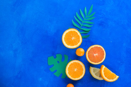 Exotic fruits close-up. Oranges, kumquats and other tropical fruits vibrant blue background with copy space.