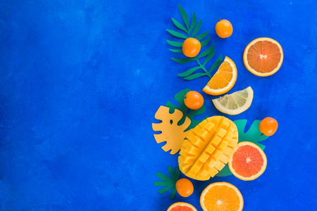 Tropic fruits on a vibrant blue background with copy space. Mango, oranges, kumquat, and other exotic fruits. 写真素材