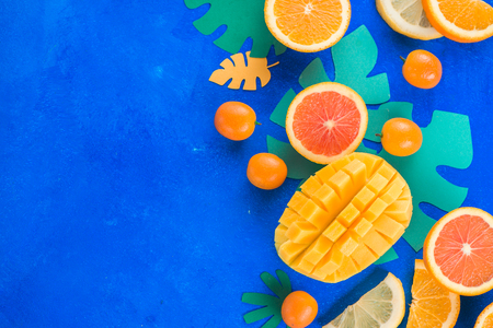 Citrus fruits, mango, oranges, kumquat, and other tropical fruits vibrant blue background with copy space. Exotic fruits close-up. 写真素材