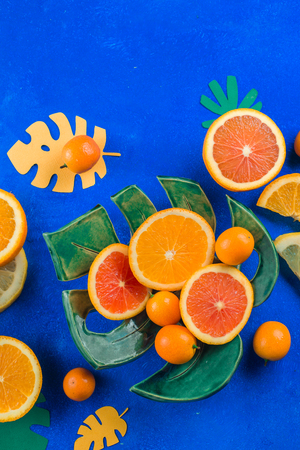 Exotic fruits close-up. Mango, oranges, kumquat and other tropical fruits vibrant blue background with copy space. 写真素材