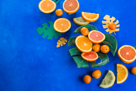 Mango, oranges, kumquat and other tropical fruits on a monstera plate. Bright blue background with copy space. Exotic food header.