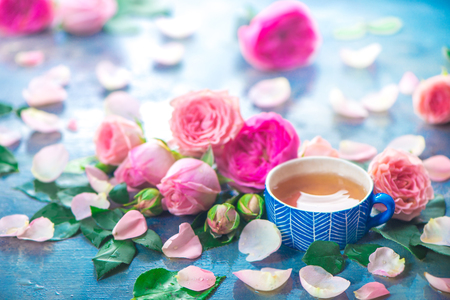 Rose tea photography with ceramic teacups and flower petals on a wet light background with copy space. Seasonal header with drink