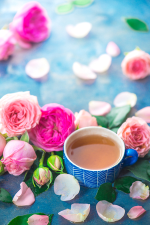 Rose tea in ceramic tea cups and flower petals on a wet light background with copy space. Seasonal drink photography
