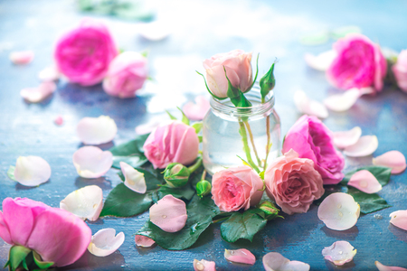 Glass bottles with pink peony roses on a light background with copy space. Feminine header with petals and flowers in pastel tones