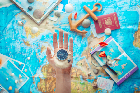 Hand holding a compass above map with wooden anchor, paper airplanes, passport and a magnifying glass. Adventure flat lay with copy space