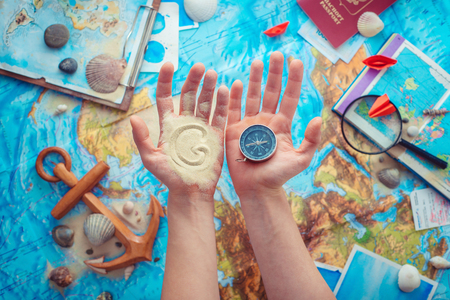Adventure and traveling concept with hands holding a world GO written with sand and a compass. Flat lay with copy space