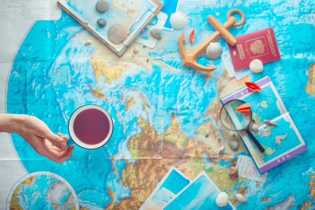 Adventure and traveling flat lay with a map, wooden anchor, paper airplanes, passport and a magnifying glass. Flat lay with copy space