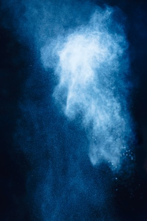 Flour powder explosion in motion. Action food photography. Light blue dust on a black background with copy space 写真素材