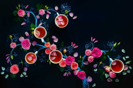 Chalk tree with tea cups and flower petals. Rose tea creative flat lay on a dark background with copy space