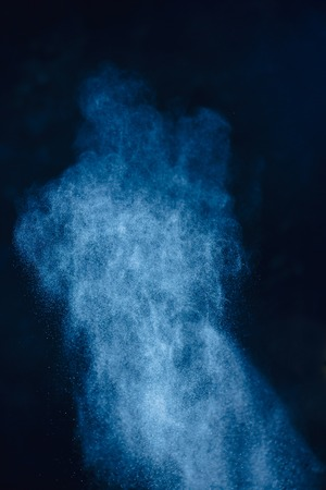 Flour powder explosion in motion. Wheat dust on a black background. Action food photography.