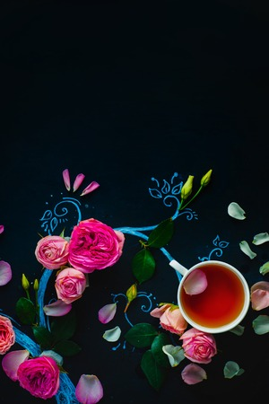 Teacups and flower petals in chalk tree flat lay. Rose tea creative flat lay on a dark background with copy space