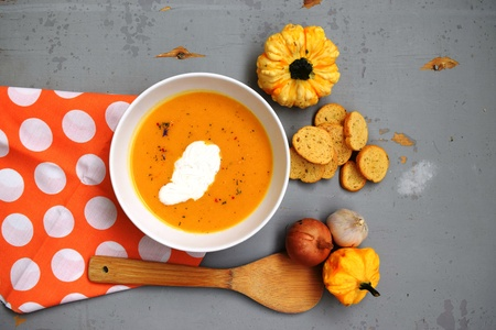 Pumpkin soup in white plate on wooden table