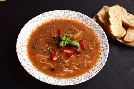 Homemade soup with beans and vegetables on a black wooden background. Stock Photo
