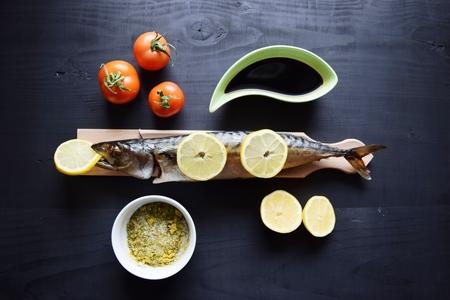 Smoked fish with lemon, on wooden board, Mackerel