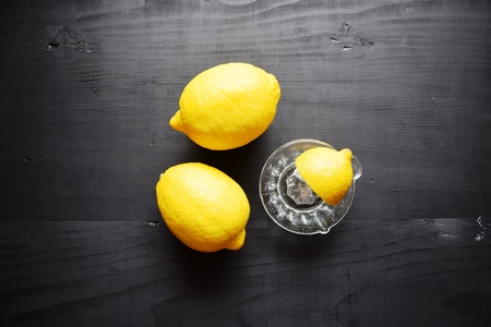 water alphabet: Lemons on a black wooden background. Fruits. The juice of the lemon . Healthy food concept,