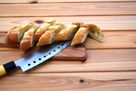 sprinkled: baguette, knife on cutting board bright wooden background