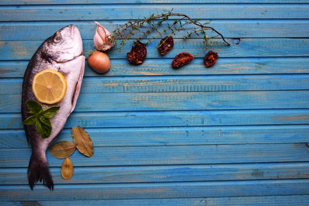 Delicious fresh fish on wood background. Fish with aromatic herbs, spices. Healthy food, diet or cooking concept