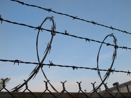 Barbed and razor wire topping a chainlink fence