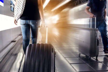 Woman drag luggage on escalator at airport. Travel planning vacation on holiday or summer concept.  Banco de Imagens