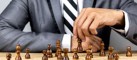 Businessman playing chess board game for development analysis new strategy planning and leader of teamwork concept for success in business.