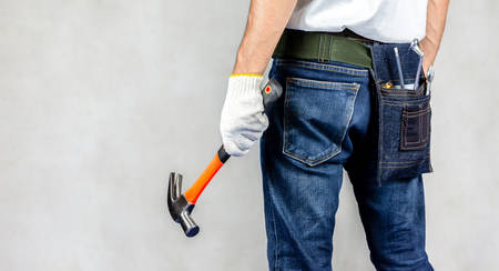 Carpenter man stand in carpentry shop with concrete background and holding hammer on hand.Labor market of joiner and craftsman concept.Free space.