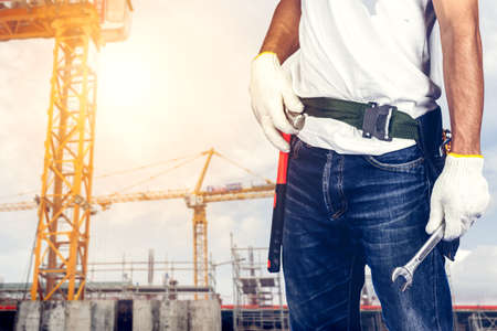 Technician man or engineer holding wrench standing on construction site.Worker inspection or control on working concept. Banque d'images