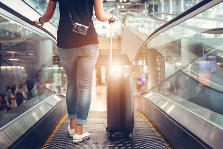 Woman drag luggage on escalator at airport.Travel planning vacation on holiday or summer concept.