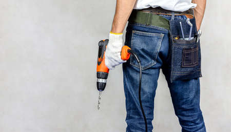 Carpenter man stand in carpentry shop with concrete background and holding drill on hand.Labor market of joiner and craftsman concept.Free space. Banque d'images