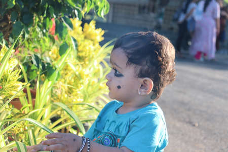 Cute hat wearing baby boy posing in front of a beautiful tropical flower.Portrait of a mixed race baby boy