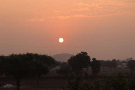 Sunset or sunrise rural farm meadow horizon view