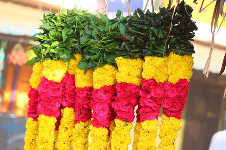 close up of green betel leaves, yellow marigold flowers, red roses flowers garland hanging for sell on the street market in the chennai, flowers garland on the street market, flower market,