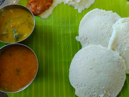 south indian food or dish ( idly with side dish ) on banana leaf, close up