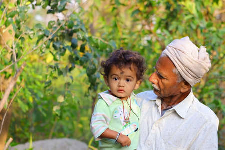 a young child and grandfather in the garden , India