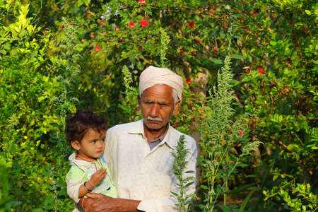 grandfather and little child standing in the home garden , India Foto de archivo