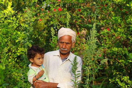 Großvater und kleines Kind stehen im Hausgarten, Indien Standard-Bild