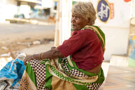 Chennai- Tamilnadu India , 24 July 2020. Old woman sitting outside the shop near road 新聞圖片