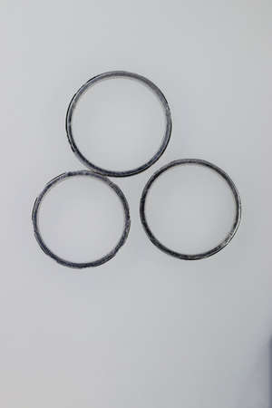 Three platinum round rings on white background
