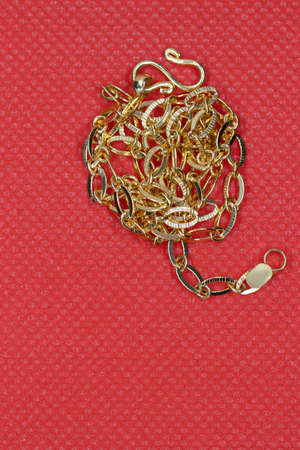 Bright gold long chain on red background