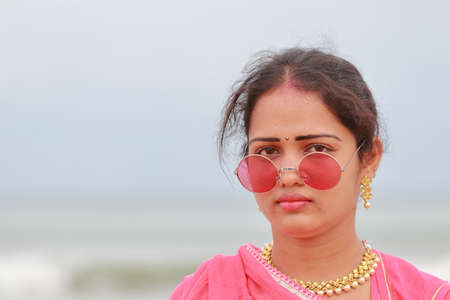 A beautiful Indian woman standing near the seashore and face glow and natural revolution Standard-Bild