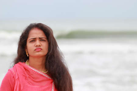 A beautiful South Indian model poses on Chennai's marina coast and defocused towards hind ocean natural background,And wearing the clothes of the culture of North India Stock Photo