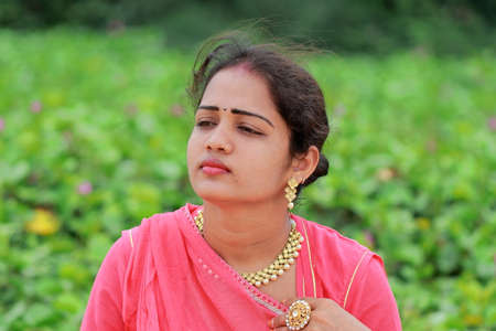 An Indian handsome female fashion model sitting in a green garden and looking away Stock Photo