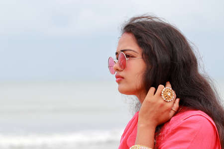 A portrait head shot of a beautiful young Indian woman standing alone on the shores of Chennai,And gorgeous lady models looking away and wearing their culture clothes, sunglasses and cosmetic apparel Stockfoto
