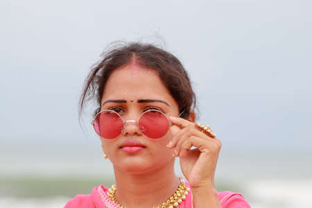 A beautiful Asian woman and wearing styles glasses over her gorgeous eyes and defocused Natural sea background in the back, closeup of indian lady