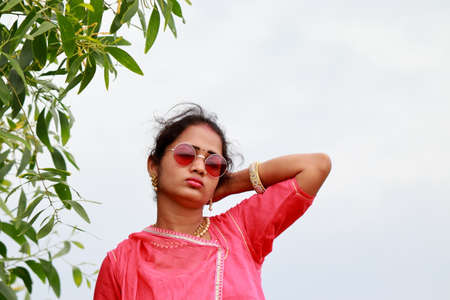 adult female model posing in a beautiful traditional dress and wearing new style sunglasses above the eyes, Summer fashion, promotion and indigenous practice of Indian culture, nature of natural beauty